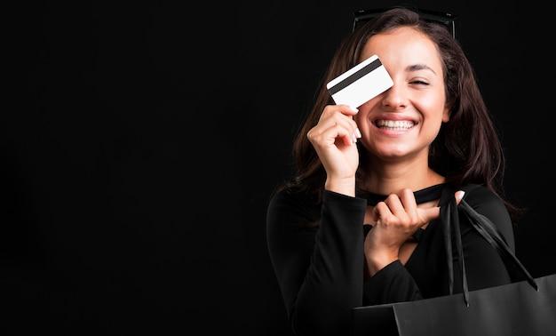 Mulher segurando sacola de compras e cartão de crédito