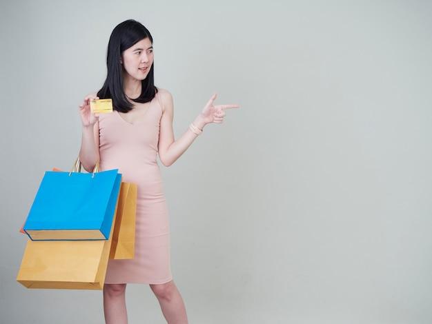 Mulher segurando sacola de compras e cartões de crédito