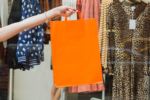 Mulher segurando sacola de compras no fundo da janela da loja