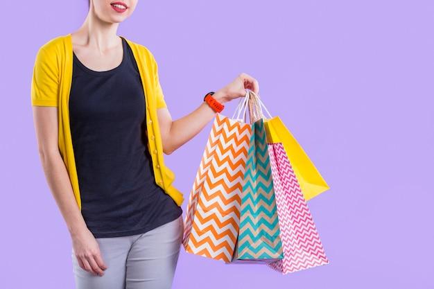 Mulher segurando sacola de papel colorido contra papel de parede roxo