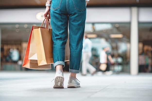 Mulher segurando sacolas de compras à venda