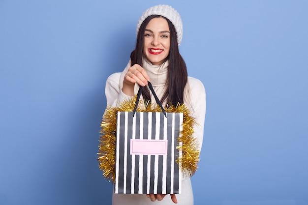 Mulher segurando sacolas de compras decoradas com enfeites de natal contra um espaço azul