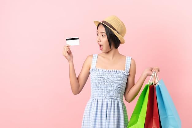 Mulher segurando sacolas de compras e cartão de crédito