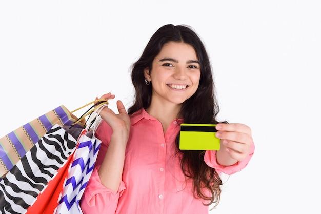 Mulher segurando sacolas de compras e cartão de crédito.