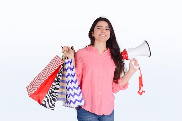 Mulher segurando sacolas de compras e megafone