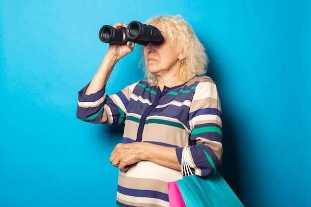 Mulher segurando sacolas de compras e olhando através de binóculos na parede azul.