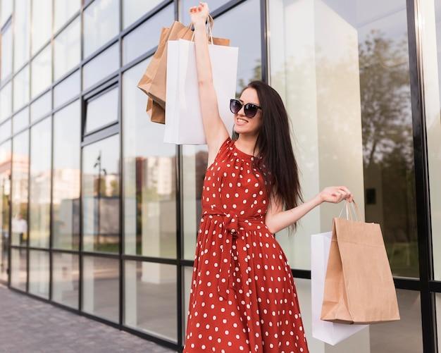 Mulher segurando sacolas de compras e olhando para longe