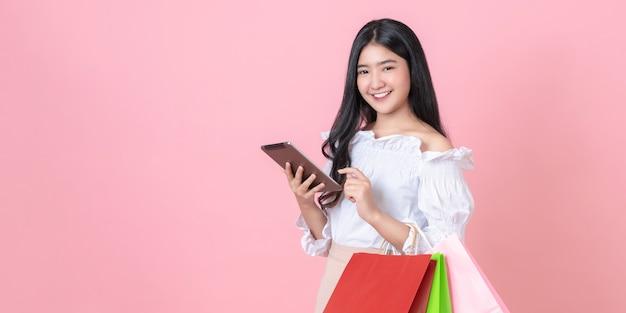 Mulher segurando sacolas de compras e tablet digital.