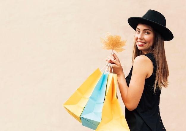 Mulher segurando sacolas de compras e uma folha com espaço de cópia