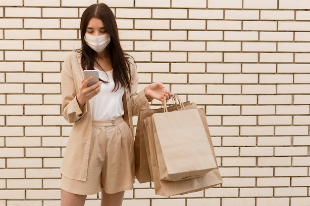 Mulher segurando sacolas de compras e usando máscara, vista frontal