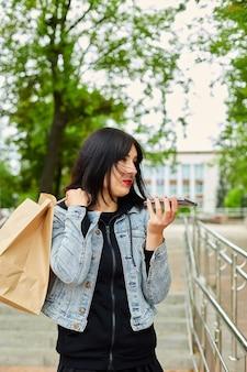 Mulher segurando sacolas de papel e falando no telefone, falando no smartphone na garota do parque depois de fazer compras