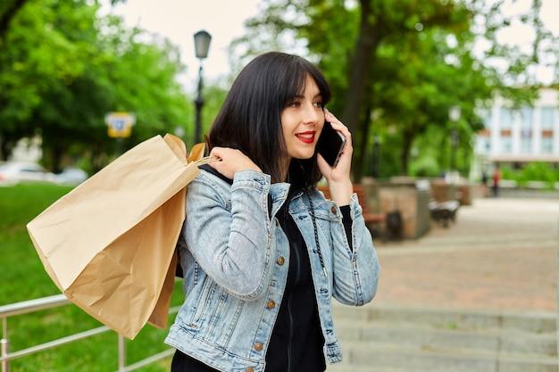 Mulher segurando sacolas de papel, falando por telefone, falando por smartphone, garota depois das compras.