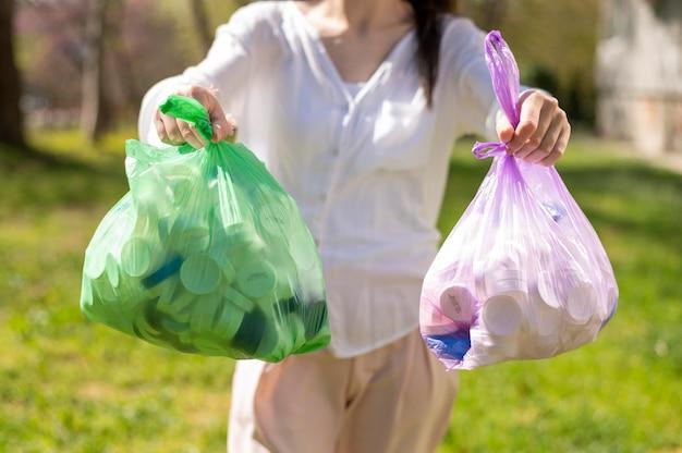Mulher segurando sacolas plásticas com lixo