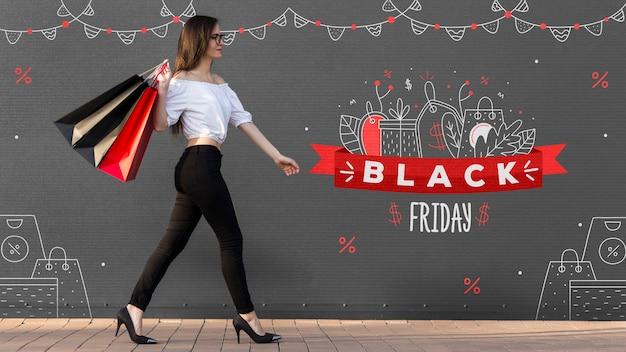 Mulher segurando sacolas pretas de compras na sexta-feira