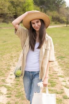 Mulher segurando sacolas reutilizáveis na natureza