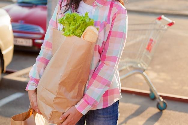 Mulher segurando sacos de papel com compras perto de um supermercado.