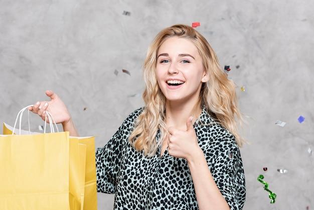 Mulher segurando sacos de papel e olhando para o fotógrafo