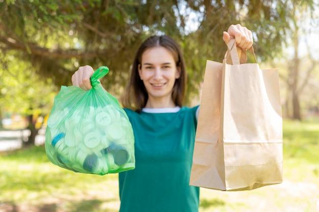 Mulher segurando sacos de papel e plástico