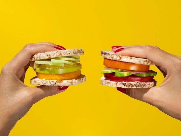 Mulher segurando sanduíches saudáveis em fundo amarelo