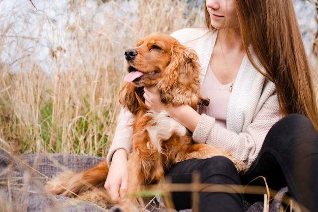 Mulher segurando seu cachorro ao ar livre