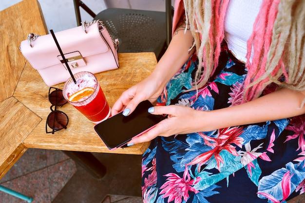 Mulher segurando seu smartphone e bebendo uma limonada saborosa