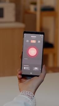 Mulher segurando smartphone com aplicativo de controle de iluminação