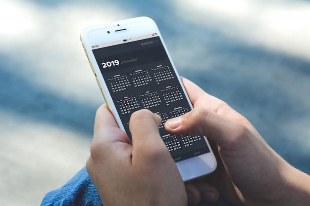 Mulher segurando smartphone com calendário app