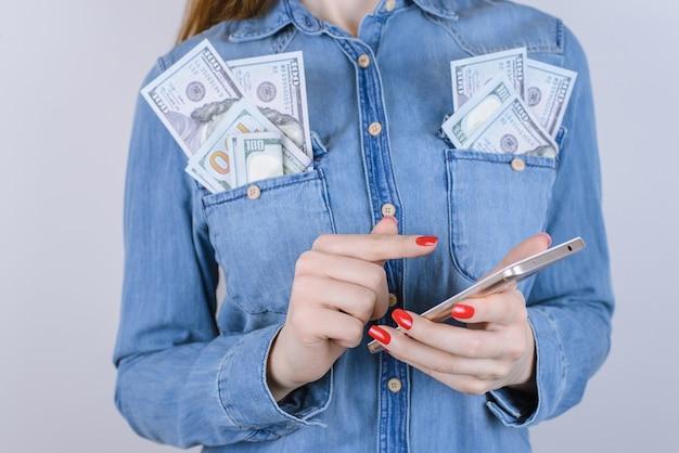 Mulher segurando smartphone com notas de cem dólares nos bolsos