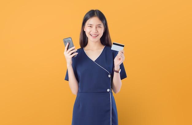 Mulher segurando smartphone e cartão de crédito em fundo laranja