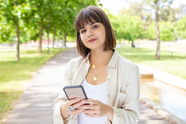 Mulher segurando smartphone e sorrindo no parque