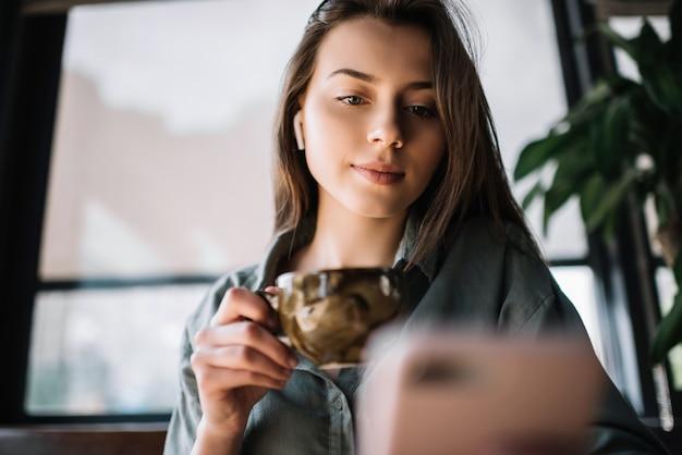 Mulher segurando smartphone, lendo notícias, tomando café no café