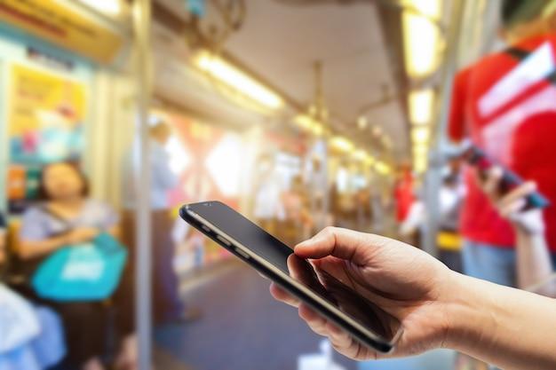 Mulher segurando smartphone na estação bts skytrain