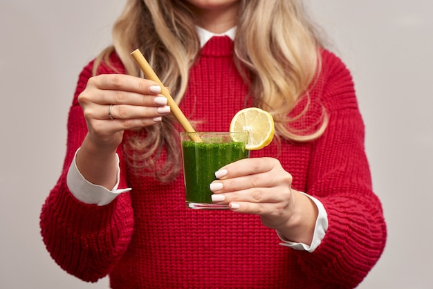Mulher segurando smoothie de espinafre fresco verde com palha de bambu