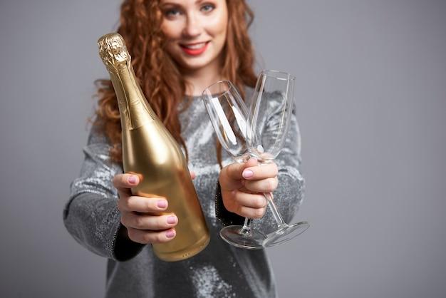 Mulher segurando taça de champanhe e garrafa
