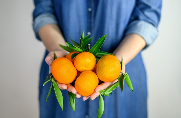 Mulher segurando tangerinas laranja com folhas nas mãos em vestido de calça jeans.