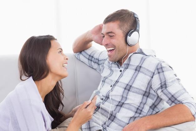 Mulher segurando telefone celular enquanto o homem escuta música