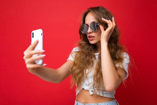 Mulher segurando telefone celular tirando foto de selfie usando a câmera do smartphone