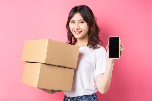 Mulher segurando telefone e caixa de carga rindo alegremente