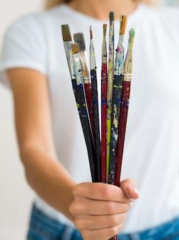 Mulher segurando tinta escovada na mão