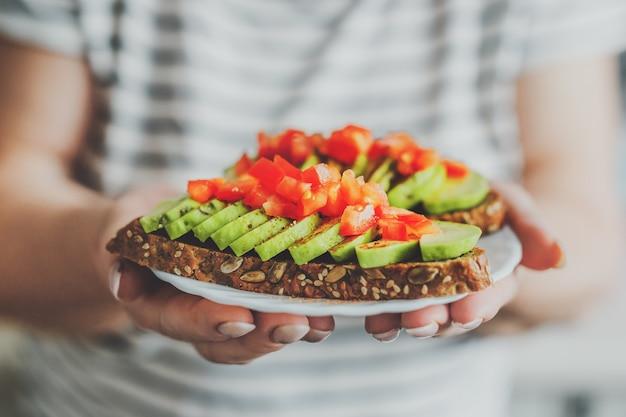 Mulher segurando torradas com abacate e tomate no prato.