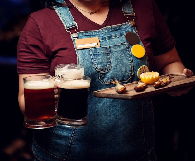 Mulher segurando três canecas de cerveja e prato de peixe defumado com limão