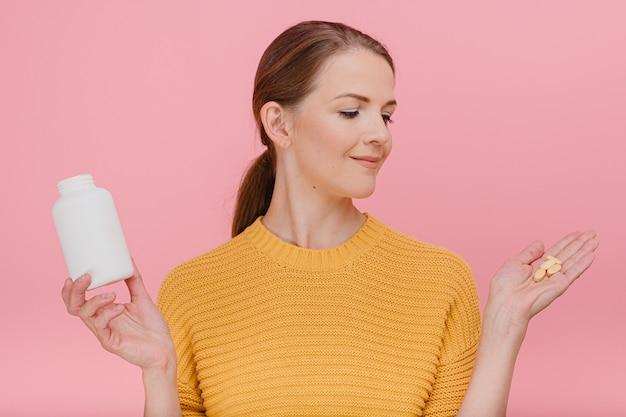 Mulher segurando tubo com vitaminas e pílulas na palma da mão usa suéter amarelo