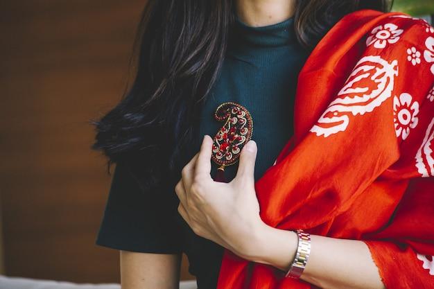 Mulher segurando um alfinete de joia em formato de buta