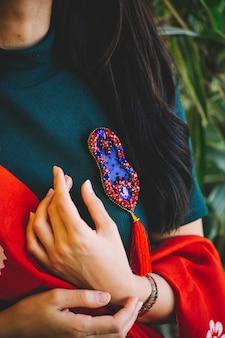 Mulher segurando um alfinete vermelho com pedras