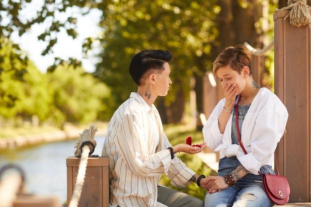 Mulher segurando um anel de noivado e fazendo proposta para a namorada enquanto eles têm um encontro no parque