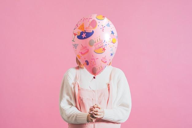 Mulher segurando um balão festivo em fundo rosa simples