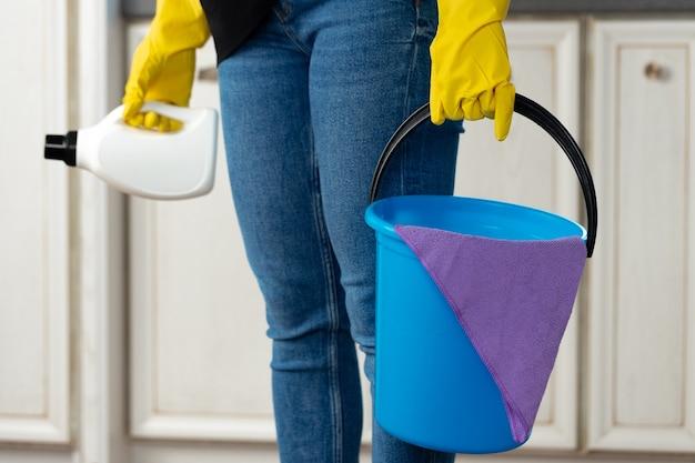 Mulher segurando um balde com detergentes líquidos