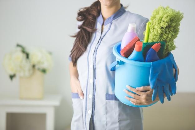 Mulher segurando um balde com produtos de limpeza