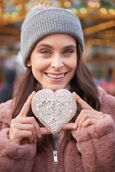Mulher segurando um biscoito de gengibre em formato de coração