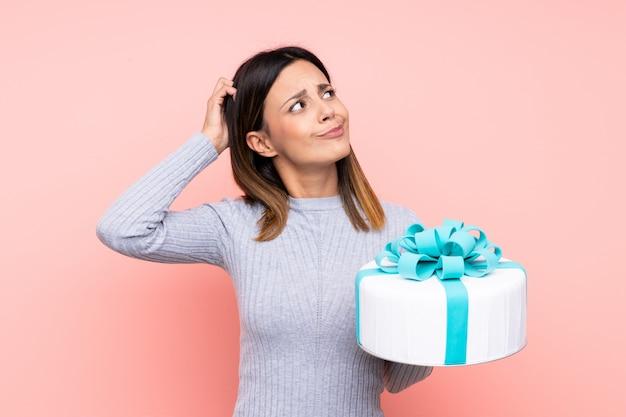 Mulher segurando um bolo grande com dúvidas e com a expressão do rosto confuso